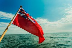 Uk red ensign the british maritime flag flown from yacht. The uk red ensign the british maritime flag flown from yacht sail boat, blue sky and baltic sea. Summer Royalty Free Stock Image
