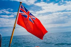 Uk red ensign the british maritime flag flown from yacht. The uk red ensign the british maritime flag flown from yacht sail boat, blue sky and baltic sea. Summer Stock Images