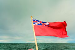 Uk red ensign the british maritime flag flown from yacht. The uk red ensign the british maritime flag flown from yacht sail boat, blue sky and baltic sea. Summer Stock Photography
