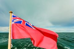 Uk red ensign the british maritime flag flown from yacht. The uk red ensign the british maritime flag flown from yacht sail boat, blue sky and baltic sea. Summer royalty free stock images
