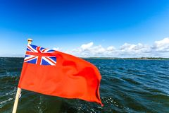 Uk red ensign the british maritime flag flown from yacht. The uk red ensign the british maritime flag flown from yacht sail boat, blue sky and baltic sea. Summer stock image