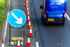 UK Road Services Roadworks Cones and directional Signs on motorway with blue van passing.  stock photo