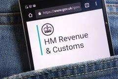 UK rządowa strona internetowa dla HM dochód i zwyczaje wystawiający na smartphone chującym w cajgach wkładać do kieszeni obraz stock