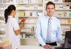 Uk-sjuksköterska och pharmacist som fungerar i apotek Arkivbild