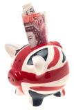 UK sjunker det piggy porslinet packar ihop med sedeln Fotografering för Bildbyråer