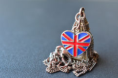 UK souvenir. Souvenir from Great Britain - necklace with pendant of Big Ben figure and heart shaped British flag on gray metal surface with shallow depth of Stock Image