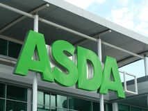 ASDA green sign logo. UK supermarket ASDA sign in the daytime against blue sky and clouds Royalty Free Stock Photography