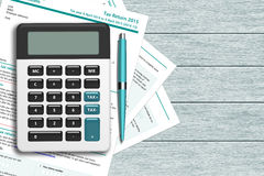 UK tax form with calculator lying on wooden desk Stock Photos