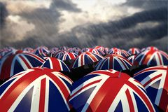 UK Umbrella Flags. A sea of United Kingdom / Union Jack umbrellas in a heavy rain storm. A conceptual image about tough times in the UK Royalty Free Stock Image