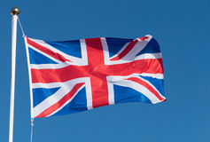 UK Union Flag of Great Britain blowing in the wind. UK Union Flag of Great Britain blowing in the wind against blue sky Stock Photo