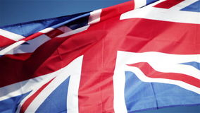 UK Union flag (Union Jack). Video footage of a UK Union flag (Union Jack) flying in the breeze atop a flagpole set against a bright blue partially clouded sky stock footage