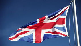 UK Union flag (Union Jack). Video footage of a UK Union flag (Union Jack) flying in the breeze atop a flagpole set against a bright blue partially clouded sky stock video