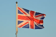 UK Union Jack Flag Flying. A UK Union Flag or Union Jack is seen flying on a flag pole on a sunny summer evening Stock Photos