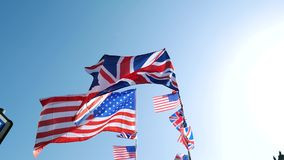 UK USA flag waving. Calm waving of British Union Jack and American flags of the United States waving slow motion against blue sky on a warm clear sky sunny day