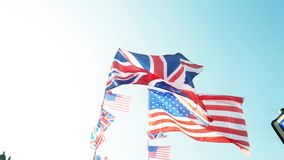 UK USA flag waving. Newsworthy British Union Jack and American flags of the United States waving slow motion against blue sky on a warm clear sky sunny day stock footage