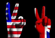 UK And USA Victory. A conceptual image of a pair of hands with UK and USA flags, showing what could be victory,freedom and peace finger gestures Royalty Free Stock Photo