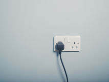 UK wall socket and cord on blue wall Royalty Free Stock Photos