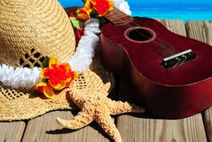 Ukelele and beach hat on dock royalty free stock photo
