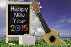 Ukelele con el cielo azul y el texto de la pizarra 2015 en la hierba Foto de archivo