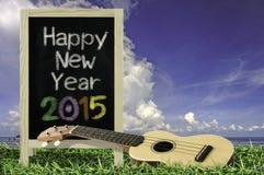 Ukelele con el cielo azul y el texto de la pizarra 2015 en la hierba Fotos de archivo