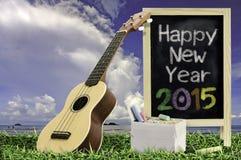 Ukelele con el cielo azul y el texto de la pizarra 2015 en la hierba Fotos de archivo libres de regalías