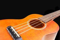 Ukelele, guitarra hawaiana, en fondo negro Fotografía de archivo libre de regalías