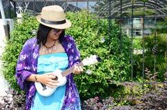 Ukelele tailandés del juego de la mujer o pequeña guitarra acústica Fotografía de archivo libre de regalías
