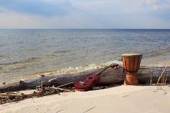 Ukelele y tambor étnico en una playa soleada Fotos de archivo