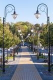 Cozy Old Town alley with rows of lanterns and benches. Ukmerge, Lithuania - October 23, 2013: Park alley perspective view in Ukmerge Lithuania Royalty Free Stock Photos