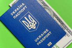Ukraiński biometryczny paszport z sto dolarowymi rachunkami na zielonym tle fotografia royalty free