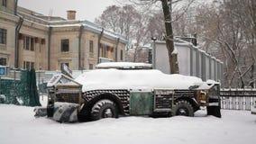 Ukraiński militarny wyposażenie zakrywający z śniegiem, niszczącym w bitwie zbiory