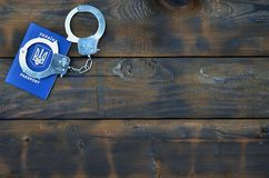Ukraiński paszport z policja kajdankami kłama na drewnianym stole Problemy z prawem podczas skrzyżowania granicy co Obrazy Royalty Free