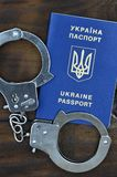 Ukraiński paszport z policja kajdankami kłama na drewnianym stole Problemy z prawem podczas skrzyżowania granicy co Zdjęcia Stock