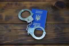 Ukraiński paszport z policja kajdankami kłama na drewnianym stole Problemy z prawem podczas skrzyżowania granicy co Obrazy Stock