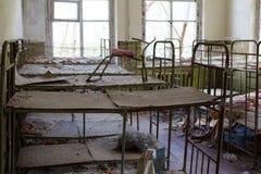 Ukraina Chernobyl niedopuszczenia strefa - 2016 03 19 Łóżka polowe w sypialni przy zaniechanym dziecinem Zdjęcie Stock