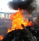 Ukraina kiev Rewolucyjność w hełmach i maski blisko płonąć opony Zdjęcia Stock