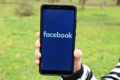 Ukraina Kremenchug - April, 2019: Flicka med smartphonen i hennes hand och en Facebook logo på skärmen bilden för nätverket 3d fr arkivfoton