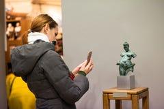 Ukraina Lviv, Grudzień, - 4, 2018: Kobieta gość fotografuje brązową rzeźbę przy muzeum zdjęcia royalty free