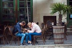 Ukraina Lviv - Maj 13, 2019: Turister smeker en katt som sitter i ett kaf? royaltyfri foto