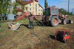 UKRAINA - MAJ 06, 2017: Den elektriska welderen reparerar grävskopan, genom att svetsa Diesel- generator för nöd- Electric Power Royaltyfri Foto