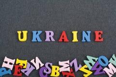 UKRAINA ord på svart brädebakgrund som komponeras från träbokstäver för färgrikt abc-alfabetkvarter, kopieringsutrymme för annons Arkivbilder