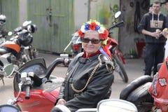 UKRAINA SHOSTKA - APRIL 28,2018: Den höga kvinnan, cyklist sitter på hennes motorcykel i den Shostka staden parkerar fotografering för bildbyråer