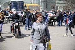 UKRAINA SHOSTKA - APRIL 28,2018: Den höga kvinnan som går nära en motorcykel, samlar i den Shostka staden parkerar Royaltyfria Bilder