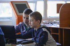 UKRAINA SHOSTKA-MAY 12,2018: Två skolbarn ser bärbara datorn på utställningen i DEN mitten royaltyfria foton