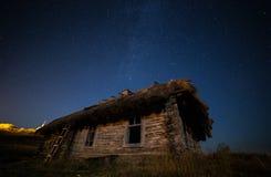 Ukrainare övergett hus i den gamla byn Mot bakgrunden av Vintergatan Arkivbild