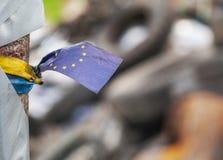 Ukrainare EUROMAIDAN 2014 Ukrainare och EU-remsor anknöt samman med barrikaddäck på bakgrunden Fotografering för Bildbyråer