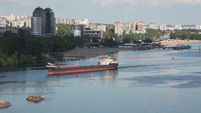 Ukraine. The city of Zaporozhye. Cargo ship sails on the river Dnieper. The cargo ship swims on the river against the background of the urban landscape. Video stock video footage
