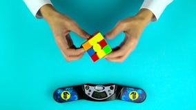 Ukraine, Dnipro 20 Feb 2019: Hands of person solving Rubik`s cube, recording time on stopwatch. Ukraine, Dnipro 20 Feb 2019: Close-up motion of a hands of an stock video