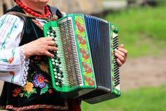 ukraine Een bejaarde in het Oekraïense kostuum speelt de harmonika bij het etnische festival in Petrikovka stock foto's