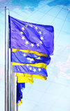 Ukraine and EU flags waving on blue sky. Royalty Free Stock Image